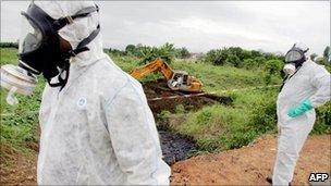 Workers walk past a contaminated road-side ditch (credit AFP)