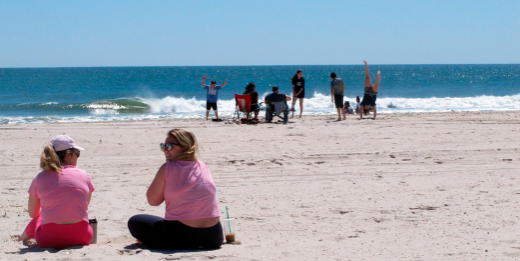 A pair of women and a family six feet apart at the New Jersey Shore.
