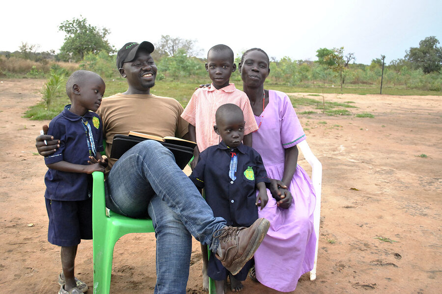 Okello pictures with kids who live in Okere